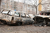 Totally destroyed and damaged cars burned in fire in the war zone or in civil demonstrations close up