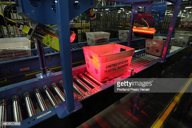A tote of mail is scanned as it travels along a conveyor belt Thursday Dec 18 2014 at the USPS sorting facility in Scarborough Maine