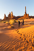 Totem Pole with rippled sand dunes at sunrise, Monument Valley, Arizona, USA