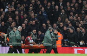 Tottenham fans abuse injured Arsenal striker Theo Walcott as he's carried off on a stretcher during the Budweiser FA Cup third round match between...