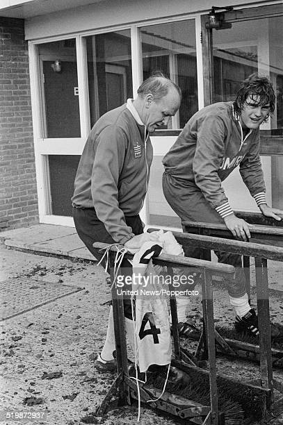 Tottenham Hotspur and England footballer Glenn Hoddle cleans his football boots with England manager Ron Greenwood during an England team training...