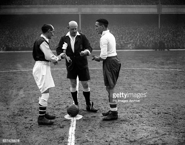 Tottenham Hotspur captain Arthur Rowe calls the coin toss before the match infront of the referee and Arsenal's captain Charlie Jones