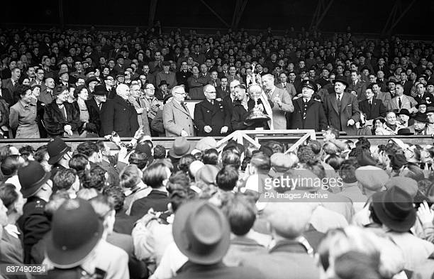 Tottenham Hotspur captain Ron Burgess is presented with the League Championship trophy