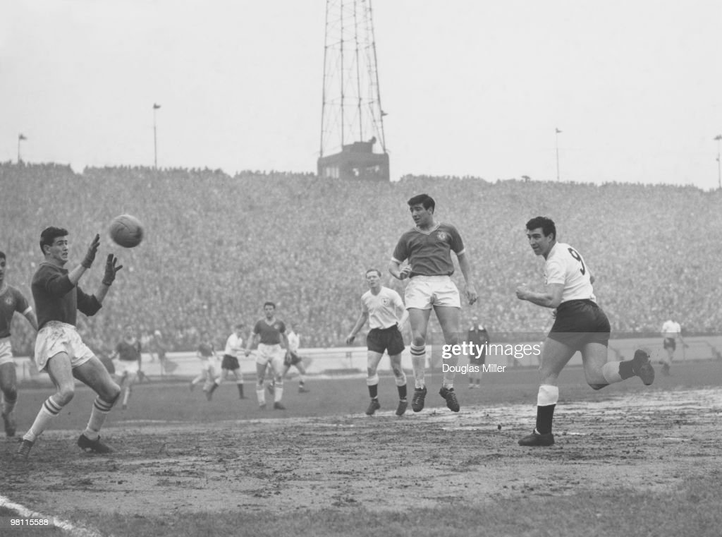 Tottenham Hotspur centre-forward Bobby Smith (right) beats Chelsea goalkeeper Peter Bonetti with a header, to score Spurs' first goal during a match at Stamford Bridge, London, 3rd April 1962. At centre is Terry Venables of Chelsea.