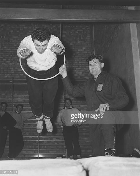 Tottenham Hotspur centreforward Bobby Smith is 'put through the hoop' by trainer Bill Watson at White Hart Lane London 2nd January 1963