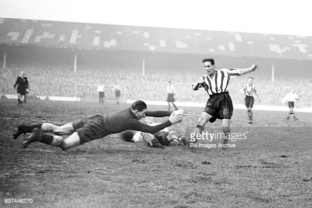 Tottenham Hotspur goalkeeper Ted Ditchburn dives at the feet of Newcastle United's George Robledo