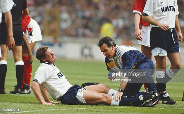 Tottenham Hotspur player Paul Gascoigne receives treatment before being stretchered off after commiting a foul on Nottingham Forest player Gary...