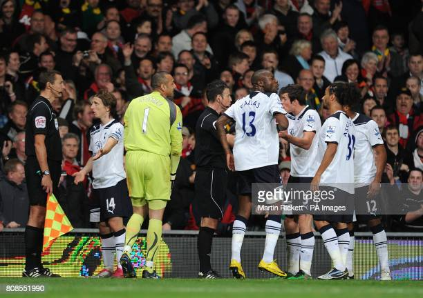 Tottenham Hotspur players argue with referee Mark Clattenburg and his assistant about Manchester United's second goal