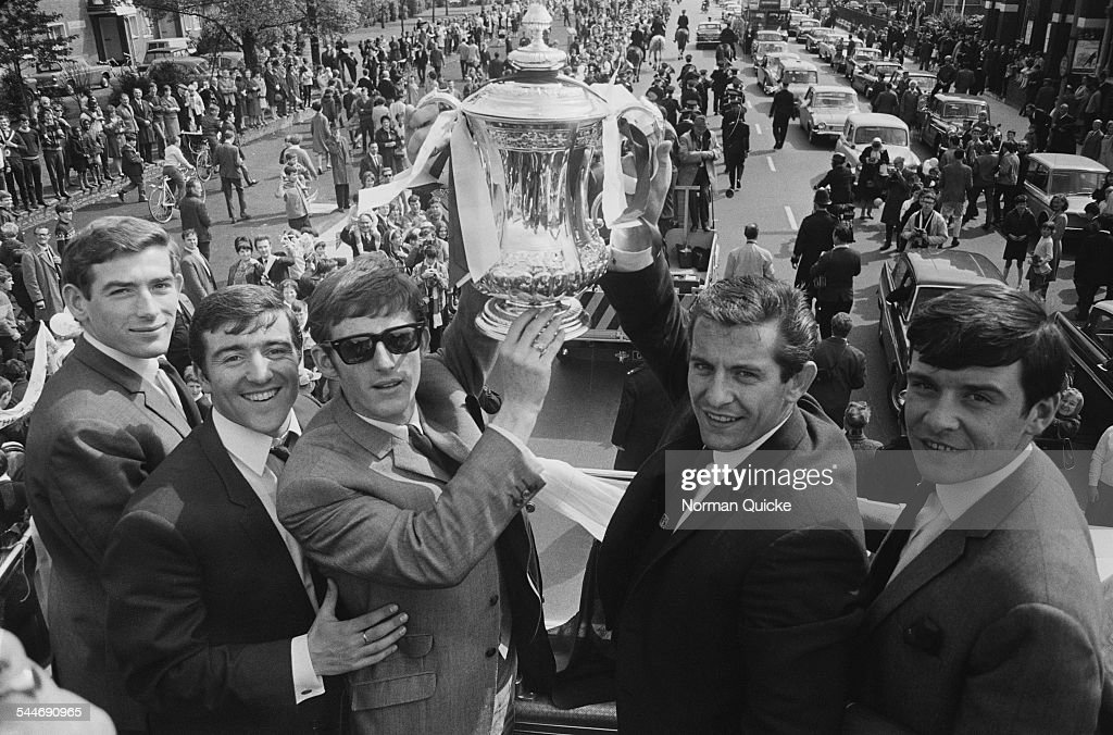 Pat Jennings, Terry Venables, Jimmy Robertson, Alan Mullery, and Cyrille Knowles (1944 - 1991) display the FA Cup trophy to jubilant fans from an open top bus en route to a civic reception at Tottenham Town Hall after they had beaten Chelsea 2-1 in the FA Cup Final, London, 20th May 1967.