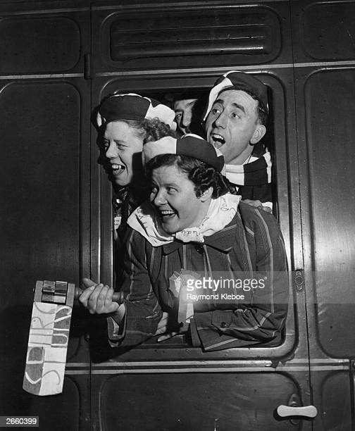 Tottenham Hotspur supporters shouting out of the window of the football 'Special' train as it pulled out of Euston Station Original Publication...