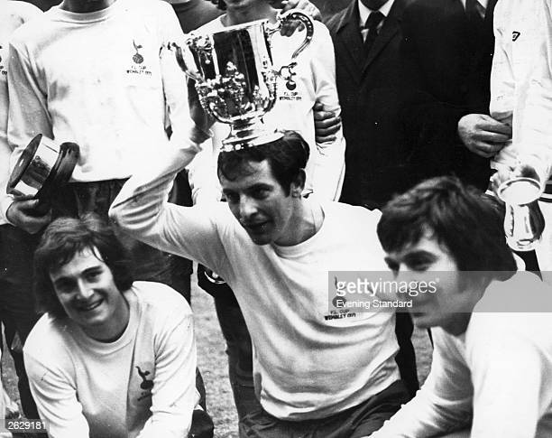 Tottenham Hotspur's Alan Mullery celebrates his side's League Cup win with his colleagues and balances the league trophy on his head