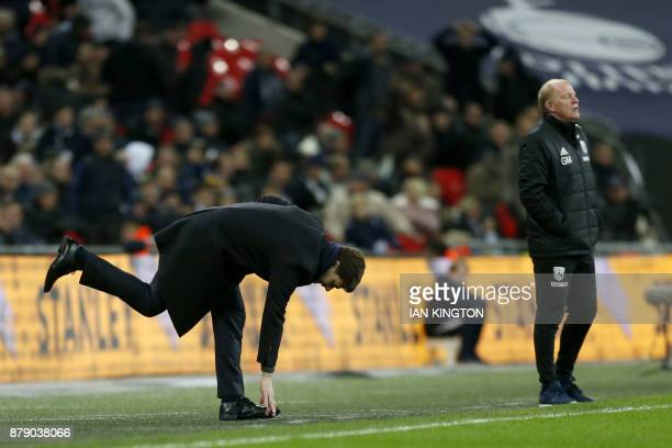 Tottenham Hotspur's Argentinian head coach Mauricio Pochettino leans over as West Bromwich caretaker coach Gary Megson looks on during the English...