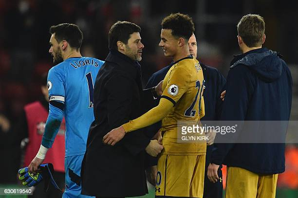 Tottenham Hotspur's Argentinian head coach Mauricio Pochettino embraces Tottenham Hotspur's English midfielder Dele Alli at the end of the English...