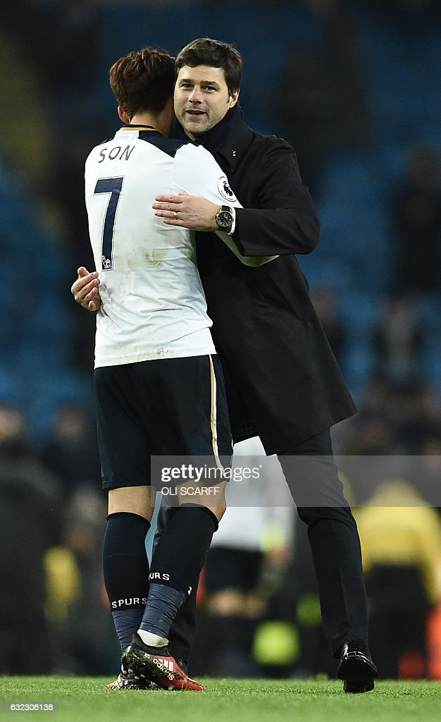 Tottenham Hotspur's Argentinian head coach Mauricio Pochettino embraces Tottenham Hotspur's South Korean striker Son Heung-Min on the pitch after the English Premier League football match between Manchester City and Tottenham Hotspur at the Etihad Stadium in Manchester, north west England, on January 21, 2017. The game finished 2-2. / AFP / Oli SCARFF / RESTRICTED TO EDITORIAL USE. No use with unauthorized audio, video, data, fixture lists, club/league logos or 'live' services. Online in-match use limited to 75 images, no video emulation. No use in betting, games or single club/league/player publications. /
