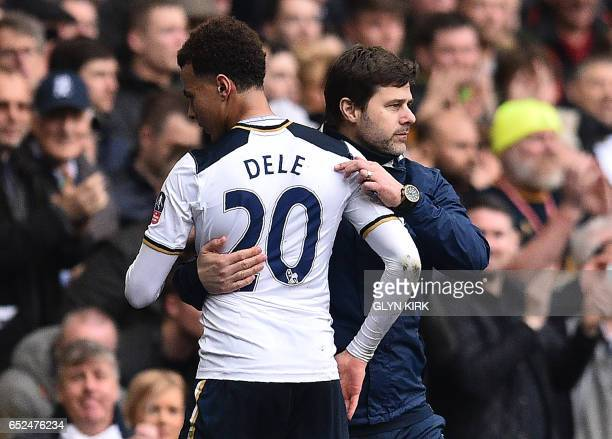 Tottenham Hotspur's Argentinian head coach Mauricio Pochettino congratulates Tottenham Hotspur's English midfielder Dele Alli as he is substituted...