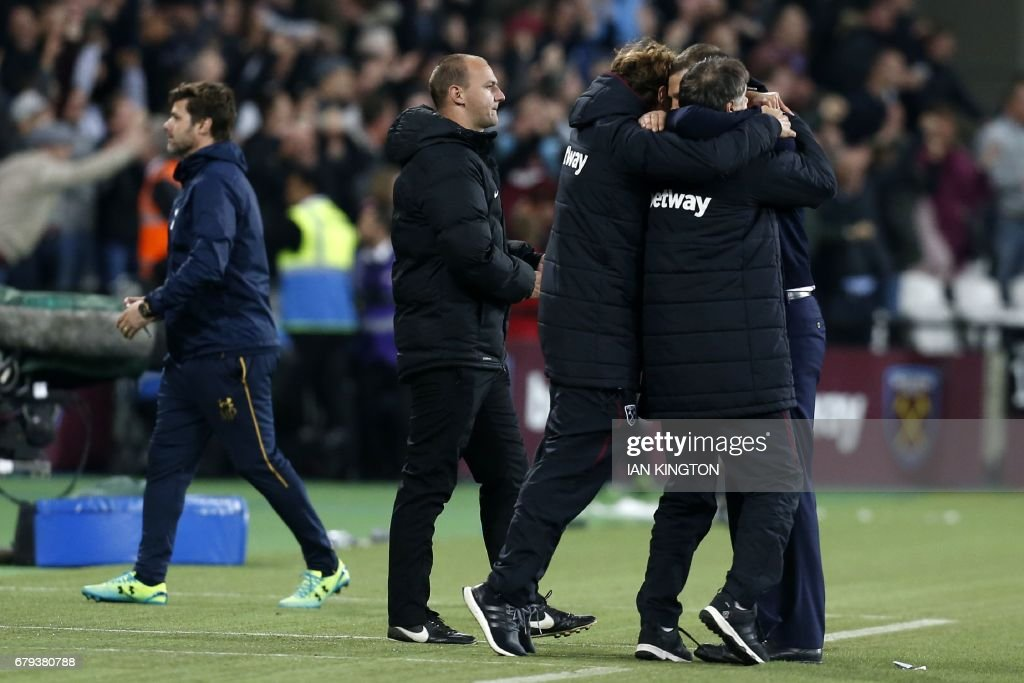 Tottenham Hotspur's Argentinian head coach Mauricio Pochettino (L) reacts as West Ham's management team celebrate after the English Premier League football match between West Ham United and Tottenham Hotspur at The London Stadium, in east London on May 5, 2017. West Ham won the game 1-0. / AFP PHOTO / Ian KINGTON / RESTRICTED TO EDITORIAL USE. No use with unauthorized audio, video, data, fixture lists, club/league logos or 'live' services. Online in-match use limited to 75 images, no video emulation. No use in betting, games or single club/league/player publications. /