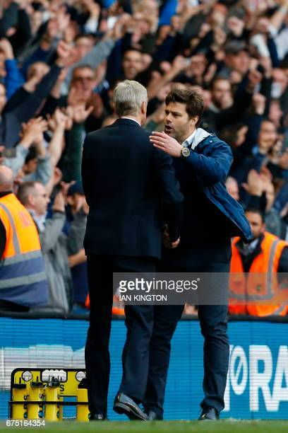 Tottenham Hotspur's Argentinian head coach Mauricio Pochettino shakes hands with Arsenal's French manager Arsene Wenger on the touchline at the end...