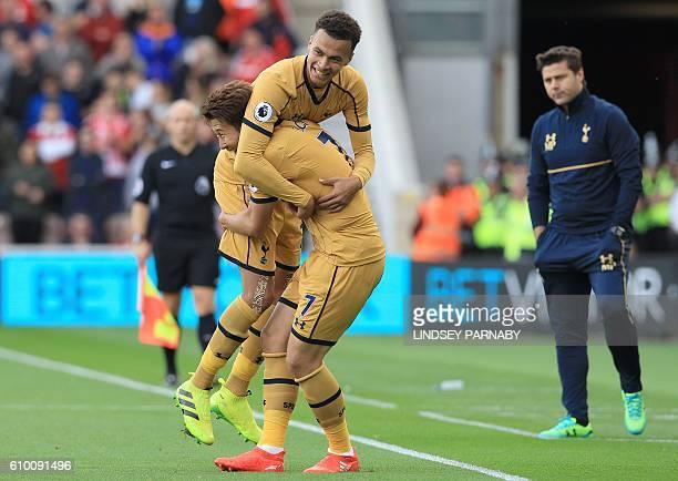 Tottenham Hotspur's Argentinian head coach Mauricio Pochettino watches as Tottenham Hotspur's South Korean striker Son HeungMin celebrates with...