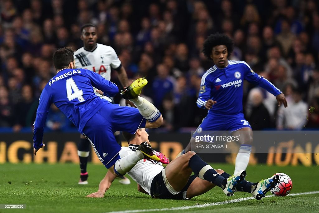 Tottenham Hotspur's Argentinian midfielder Erik Lamela (R floor) fouls Chelsea's Spanish midfielder Cesc Fabregas (L) to earn a yellow card during the English Premier League football match between Chelsea and Tottenham Hotspur at Stamford Bridge in London on May 2, 2016. / AFP / BEN STANSALL / RESTRICTED TO EDITORIAL USE. No use with unauthorized audio, video, data, fixture lists, club/league logos or 'live' services. Online in-match use limited to 75 images, no video emulation. No use in betting, games or single club/league/player publications. /