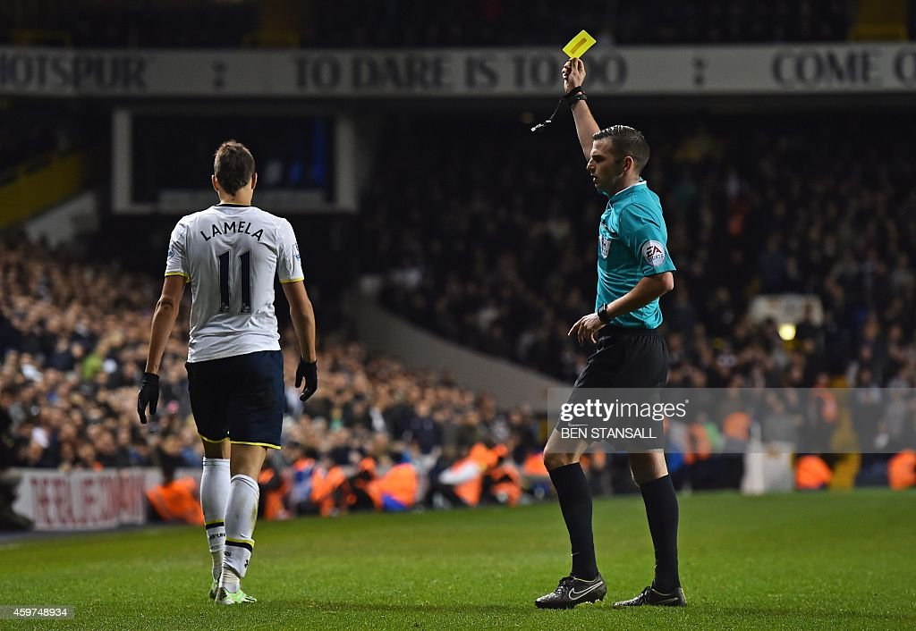 Tottenham Hotspur's Argentinian midfielder Erik Lamela receives a yellow card from referee Michael Oliver during the English Premier League football...
