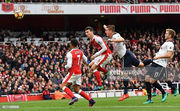 Tottenham Hotspur's Austrian defender Kevin Wimmer heads the ball past Arsenal's Chilean striker Alexis Sanchez and Arsenal's French defender Laurent...