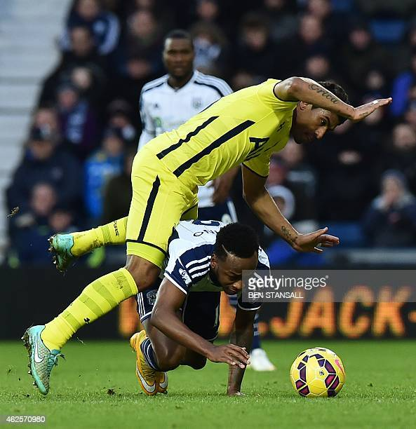 Tottenham Hotspur's Brazilian midfielder Paulinho goes over West Bromwich Albion's Burundian striker Saido Berahino during the English Premier League...