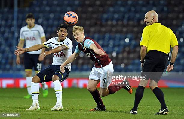 Tottenham Hotspur's Brazilian midfielder Paulinho vies with Burnley's English defender Ben Mee during the English FA Cup third round football match...