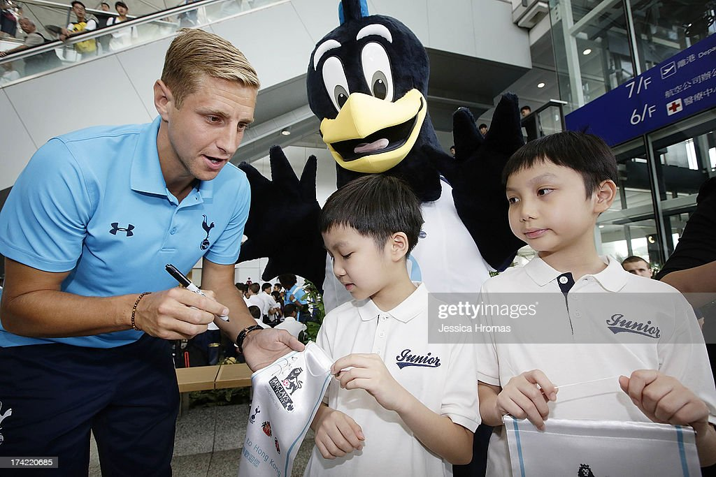 Tottenham Hotspur's captain Michael Dawson signs memorabilia for fans Sunny Wong and Kenny Wong at Hong Kong Airport, the Tottenham Hotspur team arrive to compete in the Barclays Asia Trophy, on July 22, 2013 in Hong Kong.