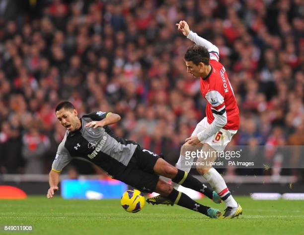 Tottenham Hotspur's Clint Dempsey is tackled by Arsenal's Laurent Koscielny during the Barclays Premier League match at the Emirates Stadium London