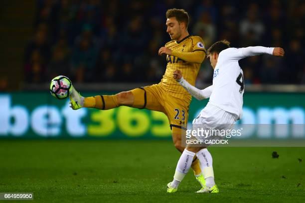 Tottenham Hotspur's Danish midfielder Christian Eriksen vies with Swansea City's English midfielder Tom Carroll during the English Premier League...