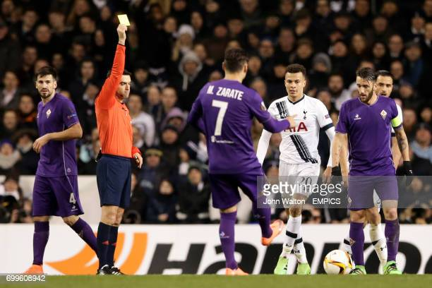 Tottenham Hotspur's Dele Alli receives a yellow card from match referee Ovidiu Hategan