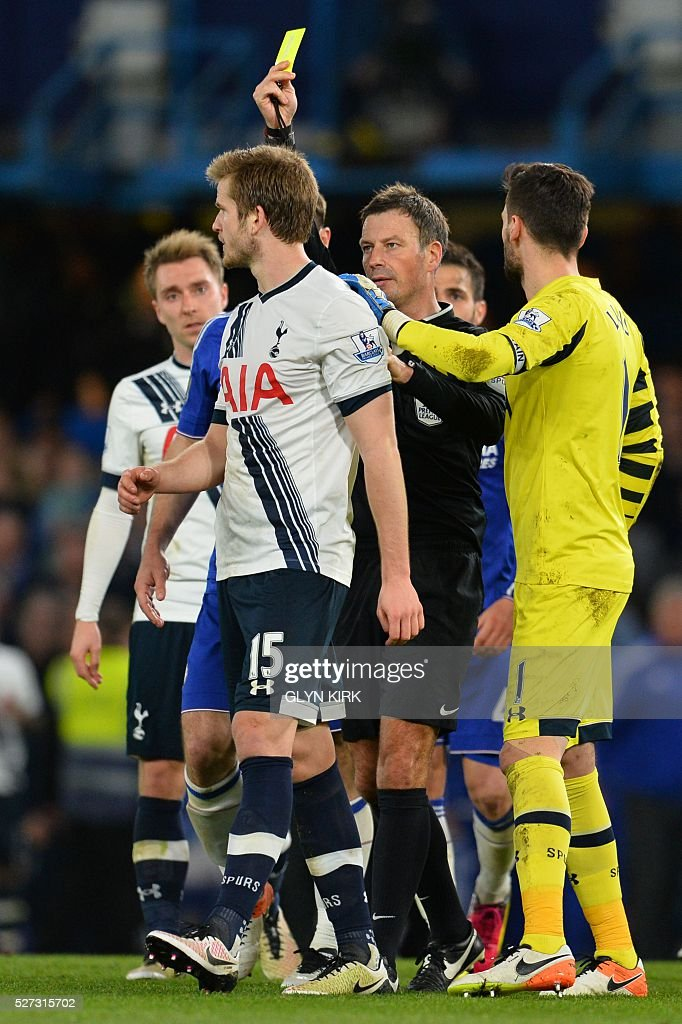 Tottenham Hotspur's English defender Eric Dier (L) is shown a yellow card by referee Mark Clattenburg (C) during the English Premier League football match between Chelsea and Tottenham Hotspur at Stamford Bridge in London on May 2, 2016. / AFP / GLYN KIRK / RESTRICTED TO EDITORIAL USE. No use with unauthorized audio, video, data, fixture lists, club/league logos or 'live' services. Online in-match use limited to 75 images, no video emulation. No use in betting, games or single club/league/player publications. /