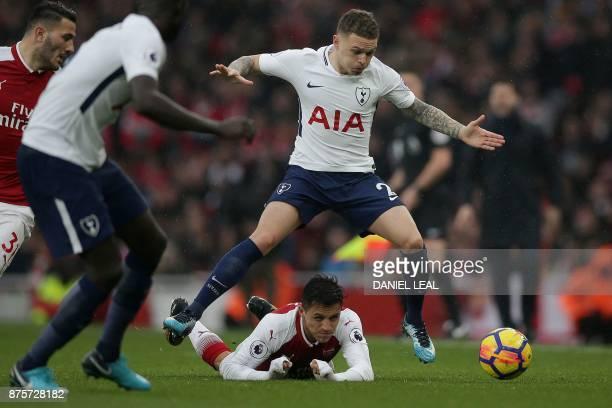 TOPSHOT Tottenham Hotspur's English defender Kieran Trippier jumps over Arsenal's Chilean striker Alexis Sanchez during the English Premier League...