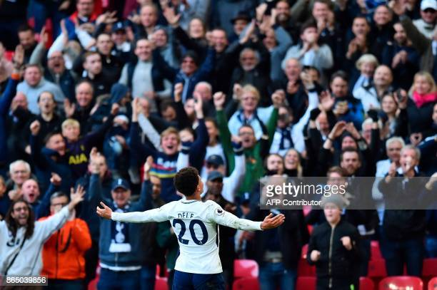 Tottenham Hotspur's English midfielder Dele Alli celebrates in front of the SPurs supporters after scoring their third goal during the English...