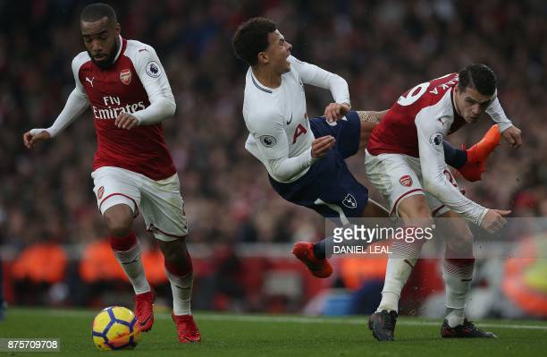 TOPSHOT Tottenham Hotspur's English midfielder Dele Alli clashes with Arsenal's Swiss midfielder Granit Xhaka as Arsenal's French striker Alexandre...