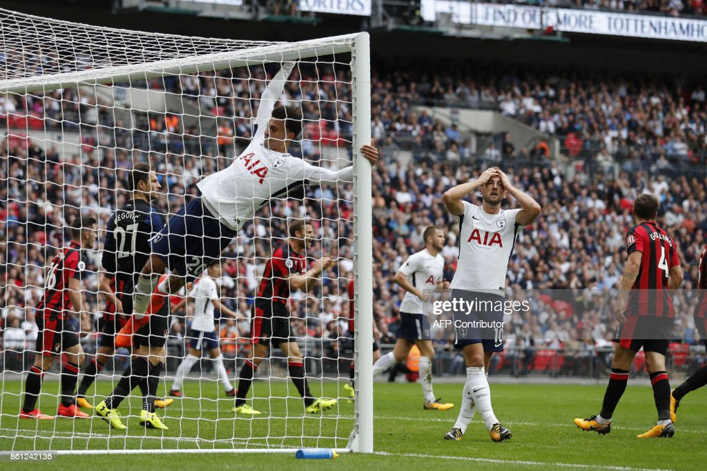 Tottenham Hotspur's English midfielder Dele Alli (L) hangs onto the goal posts as Tottenham Hotspur's English striker Harry Kane (2R) reacts to Tottenham Hotspur's Belgian defender Jan Vertonghen's cross over the top during the English Premier League football match between Tottenham Hotspur and Bournemouth at Wembley Stadium in London, on October 14, 2017. / AFP PHOTO / Adrian DENNIS / RESTRICTED TO EDITORIAL USE. No use with unauthorized audio, video, data, fixture lists, club/league logos or 'live' services. Online in-match use limited to 75 images, no video emulation. No use in betting, games or single club/league/player publications. /