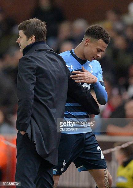 Tottenham Hotspur's English midfielder Dele Alli speaks with Tottenham Hotspur's Argentinian head coach Mauricio Pochettino as he is substituted...