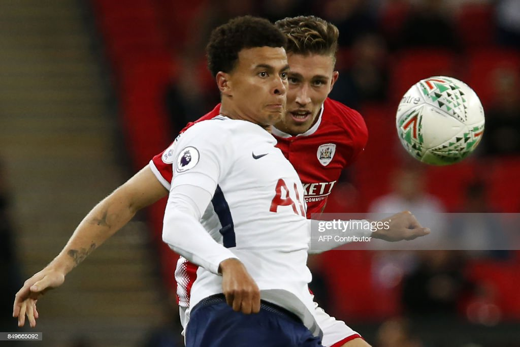 Tottenham Hotspur's English midfielder Dele Alli (L) vies with Barnsley's English defender Angus MacDonald during the English League Cup third round football match between Tottenham Hotspur and Barnsley at Wembley Stadium in London on September 19, 2017. / AFP PHOTO / IKIMAGES / Lee MILLS / RESTRICTED TO EDITORIAL USE. No use with unauthorized audio, video, data, fixture lists, club/league logos or 'live' services. Online in-match use limited to 45 images, no video emulation. No use in betting, games or single club/league/player publications. /