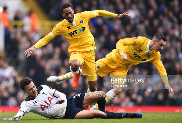 Tottenham Hotspur's English midfielder Dele Alli vies with Millwall's Englishborn Jamaican defender Shaun Cummings and Millwall's Irish midfielder...