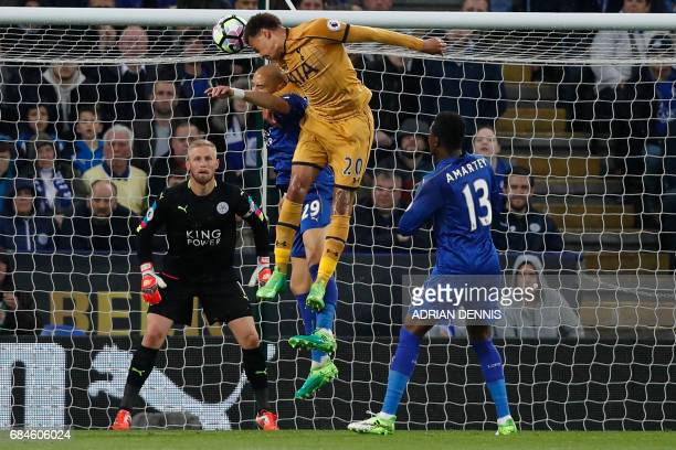 Tottenham Hotspur's English midfielder Dele Alli wins a header from Leicester City's French defender Yohan Benalouane during the English Premier...