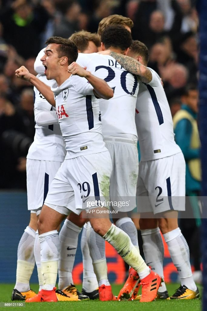 Tottenham Hotspur's English midfielder Harry Winks (L) and teammates celebrate Tottenham Hotspur's Danish midfielder Christian Eriksen's goal during the UEFA Champions League Group H football match between Tottenham Hotspur and Real Madrid at Wembley Stadium in London, on November 1, 2017. Tottenham won the game 3-1. / AFP PHOTO / Ben STANSALL
