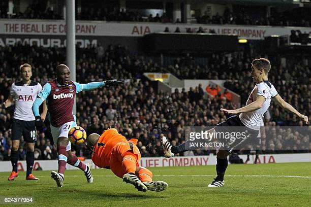 Tottenham Hotspur's English midfielder Harry Winks shoots past West Ham United's Irish goalkeeper Darren Randolph to score Tottenham's first goal...
