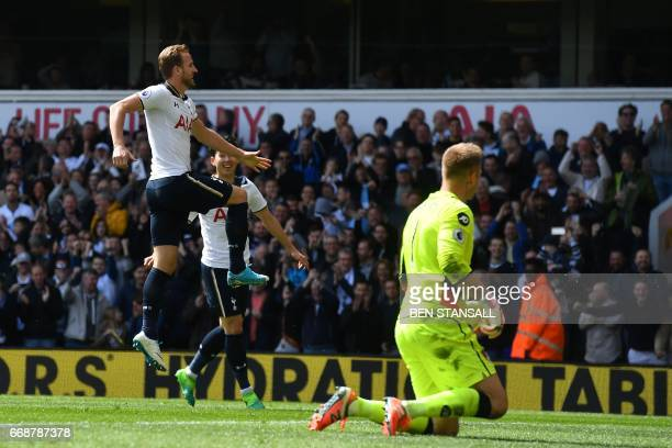 Tottenham Hotspur's English striker Harry Kane celebrates after scoring their third goal as Bournemouth's Polish goalkeeper Artur Boruc reacts during...