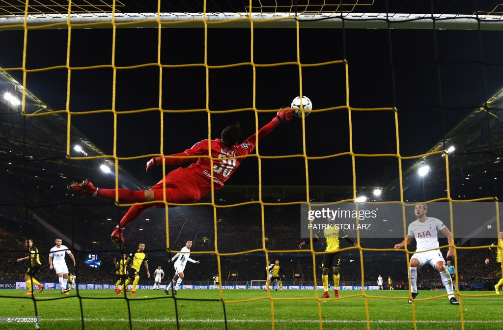 TOPSHOT - Tottenham Hotspur's English striker Harry Kane (R) looks on as Dortmund's Swiss goalkeeper Roman Buerki flys through the air to make a save during the UEFA Champions League Group H match between Borussia Dortmund and Tottenham Hotspur on November 21, 2017 in Dortmund, Germany. /