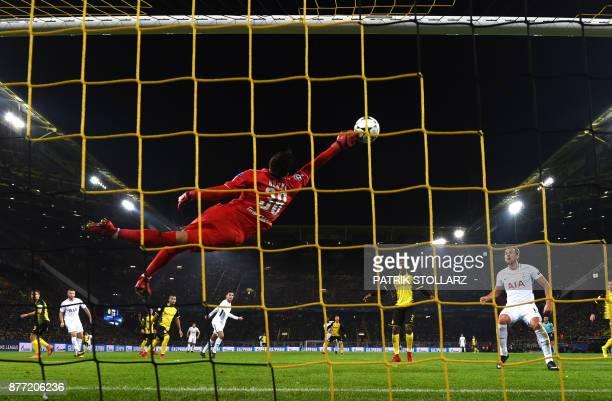 TOPSHOT Tottenham Hotspur's English striker Harry Kane looks on as Dortmund's Swiss goalkeeper Roman Buerki flys through the air to make a save...
