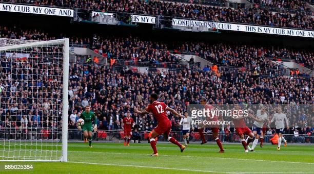 Tottenham Hotspur's English striker Harry Kane shoots to score the opening goal of English Premier League football match between Tottenham Hotspur...