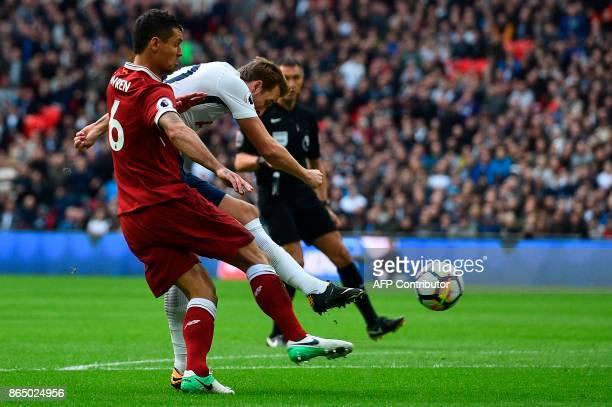 Tottenham Hotspur's English striker Harry Kane shoots under pressure from Liverpool's Croatian defender Dejan Lovren to score the opening goal of the...