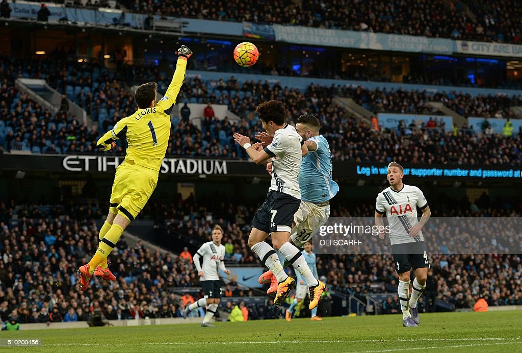 Tottenham Hotspur's French goalkeeper Hugo Lloris (L) punches the ball away from Manchester City's Argentinian defender Nicolas Otamendi (C) during the English Premier League football match between Manchester City and Tottenham Hotspur at the Etihad Stadium in Manchester, north west England, on February 14, 2016. / AFP / OLI SCARFF / RESTRICTED TO EDITORIAL USE. No use with unauthorized audio, video, data, fixture lists, club/league logos or 'live' services. Online in-match use limited to 75 images, no video emulation. No use in betting, games or single club/league/player publications. /