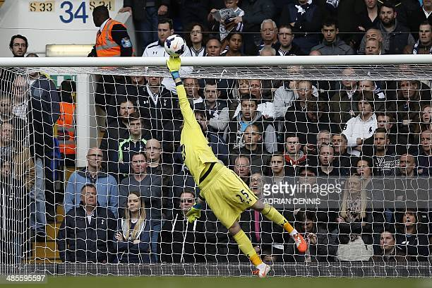 Tottenham Hotspur's French goalkeeper Hugo Lloris tips the ball over the bar to make a save during the English Premier League football match between...