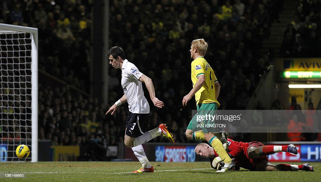 """Tottenham Hotspur's Gareth Bale (L) scores his second goal beating the goalkeeper Norwich City's John Ruddy (R) during an English Premier League football match between Norwich City and Tottenham Hotspur at Carrow Road in Norwich, east England, on December 27, 2011. USE. No use with unauthorised audio, video, data, fixture lists, club/league logos or """"live"""" services. Online in-match use limited to 45 images, no video emulation. No use in betting, games or single club/league/player publications."""